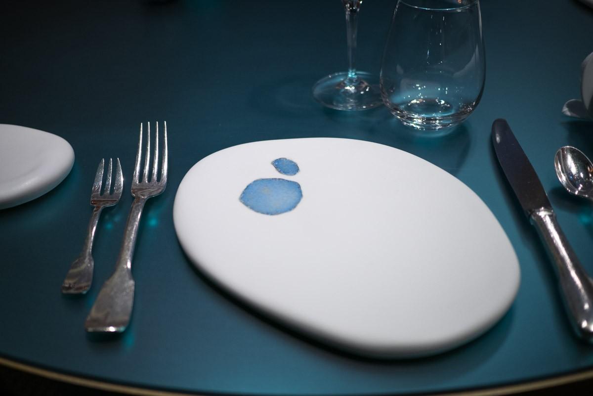 La table est bleue. Sur l'assiette de présentation, une flaque de la mer.