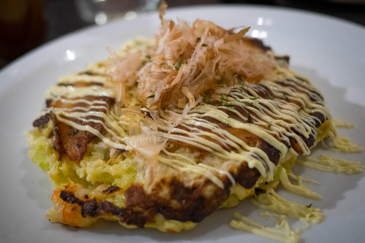 Okonomiyaki mixte porc, crevette, seiche, au natto, servi avec une sauce ponzu. Il faut d'abord cuire une couche d'okonomiyaki, mettre le natto au centre et recouvrir d'une autre couche pour que le natto garde son gluant et son parfum.