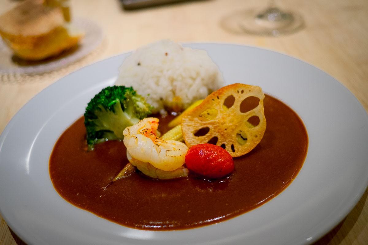 Curry chez Toyo sur fond de bouillabaisse. Juste la sauce servie avec du homard grillé, racine de lotus frite, brocoli et tomate.